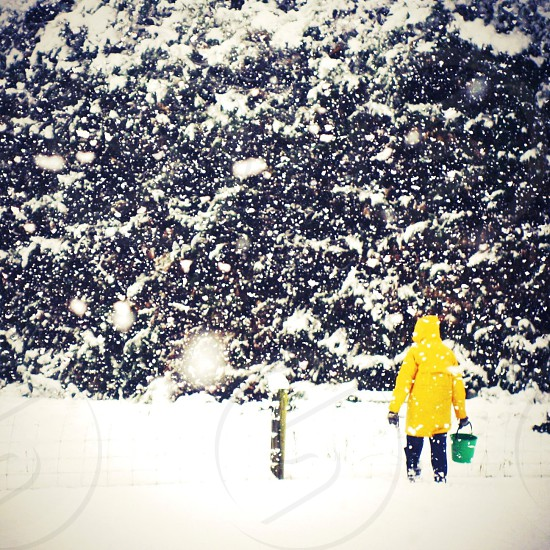 person wearing yellow hoodie walking in snow filled ground photo
