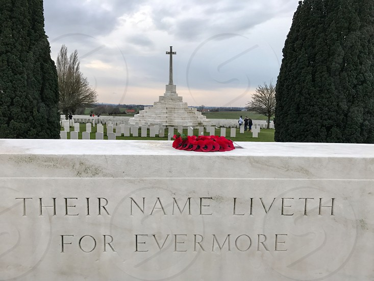 Outdoor day landscape horizontal colour Tyne Cot Cemetery Allied British Commonwealth graveyard graves gravestones memorial War remembrance white marble stone carved grass fields poppies countryside Ypres salient Europe European fields sky nature rest peace beauty silence wreath respect cross crucifix religion  photo