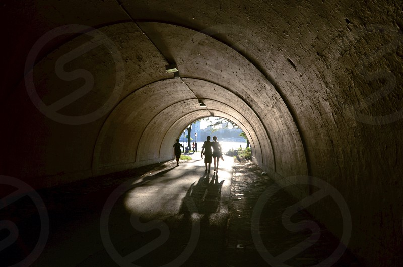 two people walking through tunnel photo