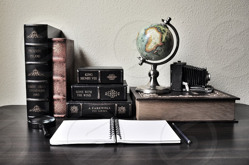 black and brown books behind white spiral book on brown wooden table photo