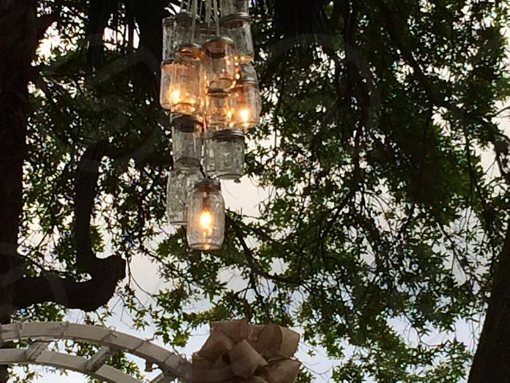 clear glass mason jar light hanging on tree photo