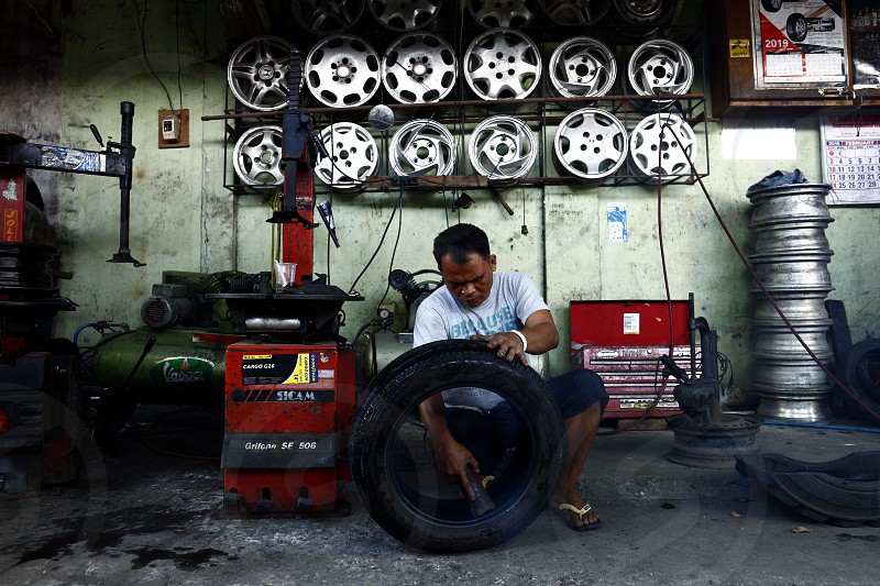 CAINTA RIZAL PHILIPPINES - MARCH 31 2019: A worker at a tire vulcanizing shop repairs a tire for a customer. photo