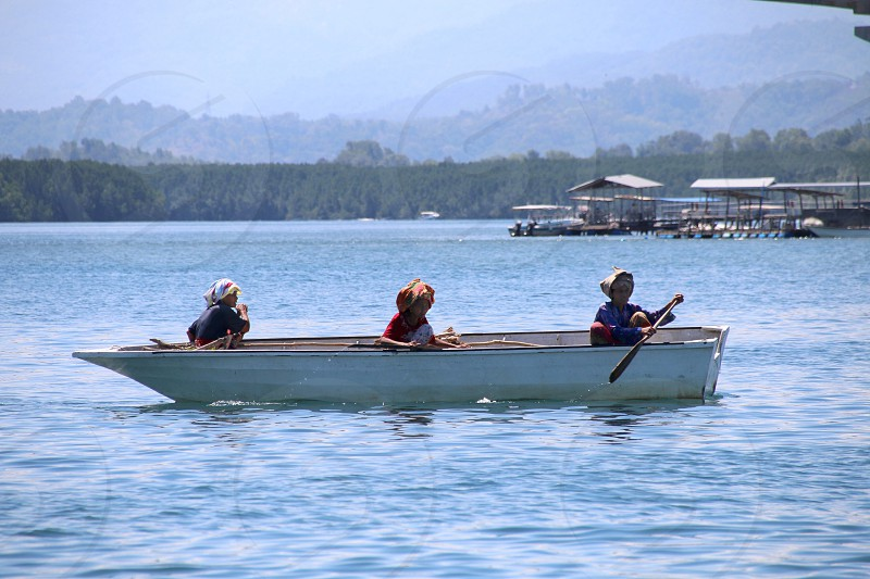 three persons riding on white boat across the blue body of water photo