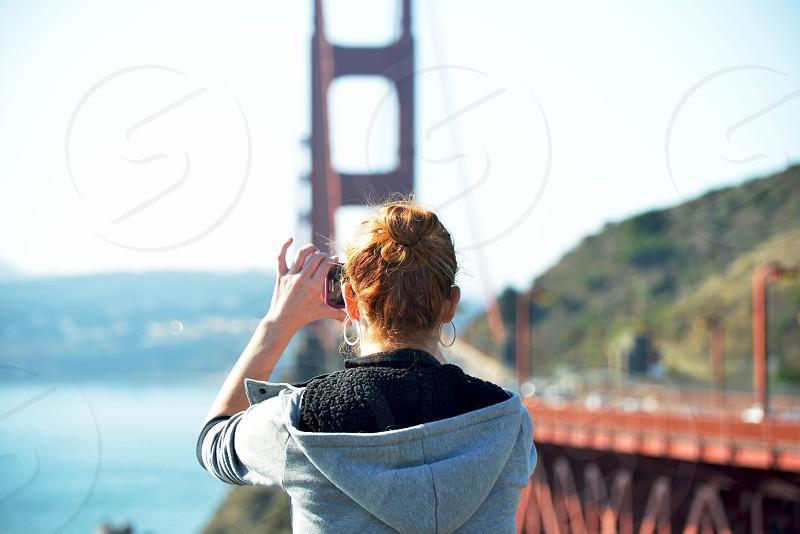 woman in grey hoodie aiming phone camera by golden gate bridge photo