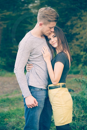 woman embracing man standing on green grass photo