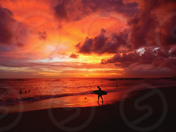 Sunset surfing swimming beach adventure sand Sky clouds holiday paradise holiday reflection landscape resort surf Surfer Surfboard travel Asia Indonesia Bali dramatic ocean sea  photo