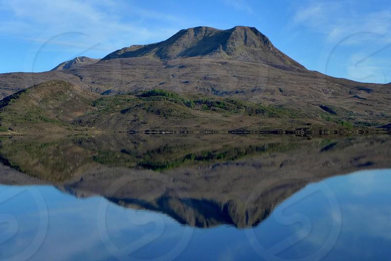 mountain mirroring body of water photo
