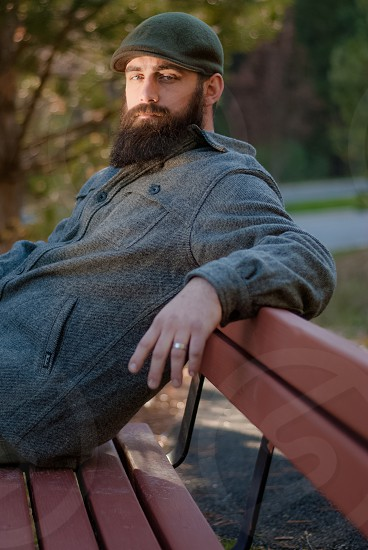 Bearded man sitting on bench in the afternoon sun photo