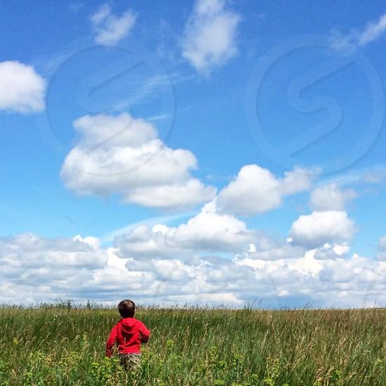 boy in red hoodie in field cloudy sky photo
