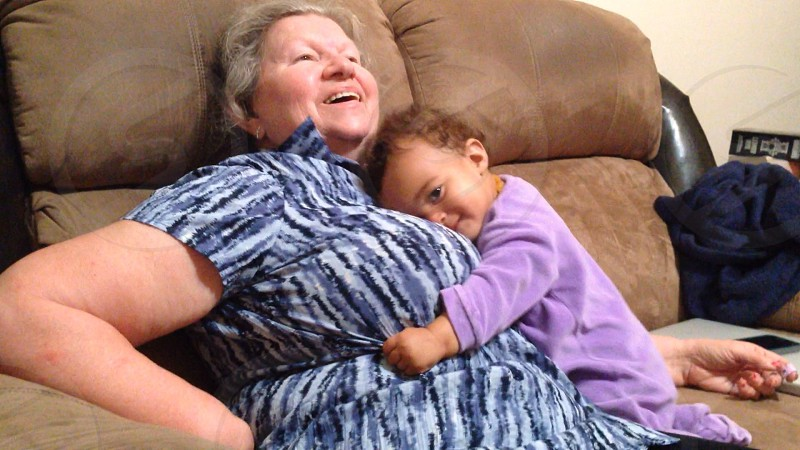 Grandmother laughing as baby cuddles with her.  photo