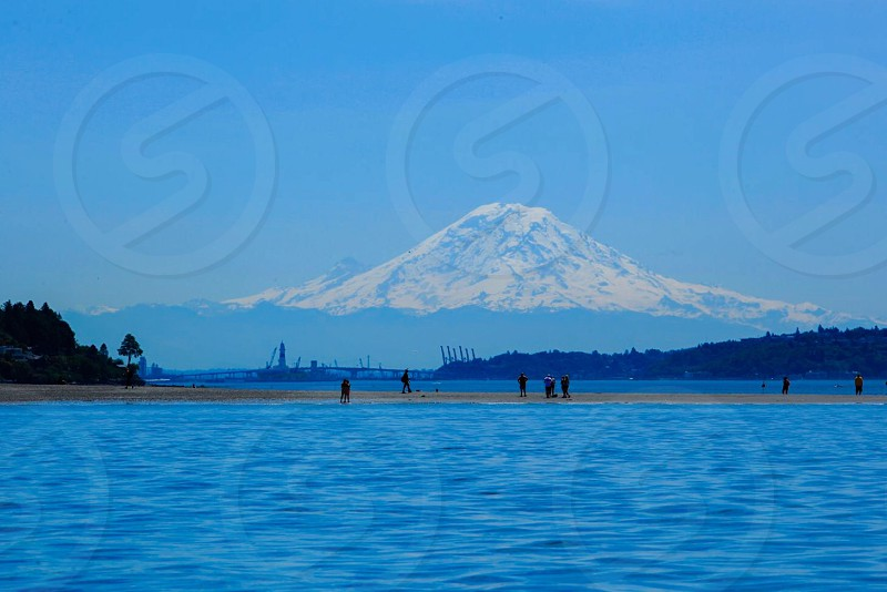 people on brown sandy shore with a white snow covered mountain on background under blue sky during daytime photo