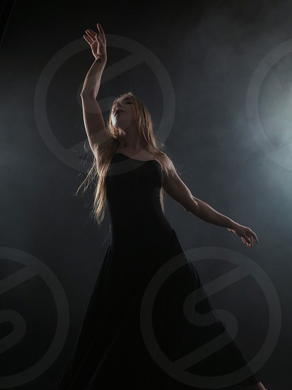 Professional ballerina dancing ballet in spotlights smoke on big stage. Beautiful caucasian young girl with long hair wearing black tight dress on floodlights background. photo