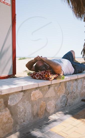 Man lying on the stone beach wall photo