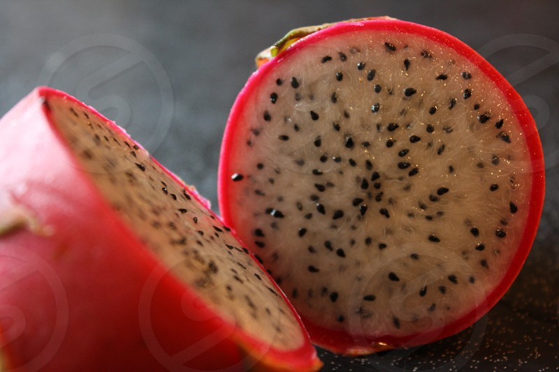 cut open dragon fruit against dark granit countertop photo