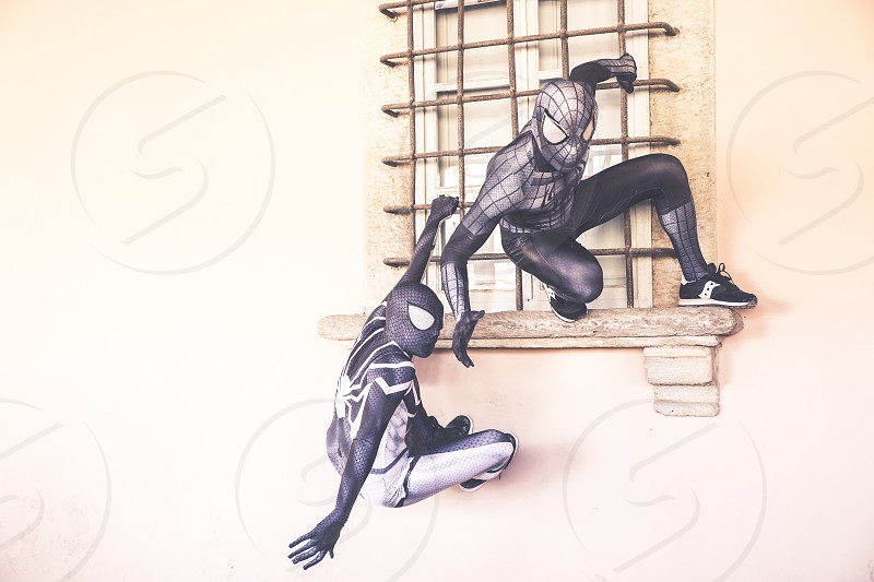 Lucca Italy 03/11/2018: Two cosplayers disguised as Spider Man perform climbing on the walls during the carnival party in Lucca photo