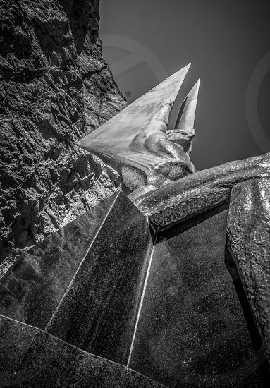 worm's eye view photoforaphy of human statue below mountain cliff in grayscale photo photo