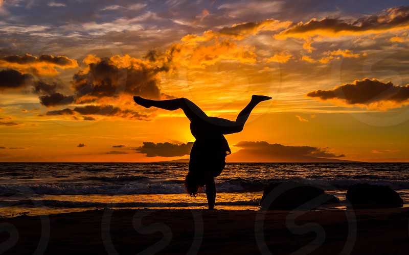 Sunset over the ocean with a handstand photo