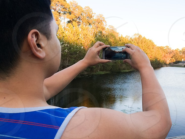 black and gray smartphone with body of water photo in screen photo