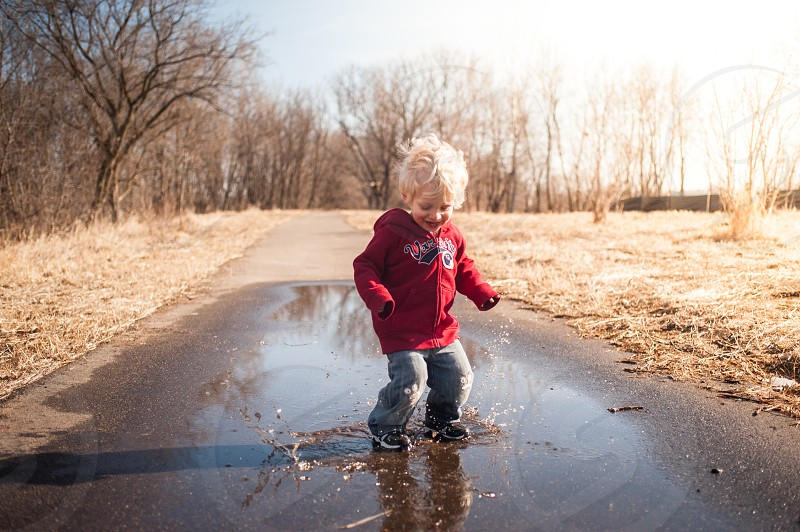 child youth boy play playing puddle water trees sensory fun sweatshirt red jeans patches splashing splash happy emotion feeling blonde photo