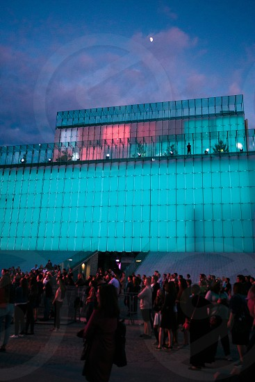 Festival event party concert with people standing on a square in a city center at night. Backlit glass construction above them photo
