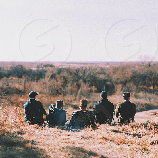 five people sitting down looking in grassy area photo
