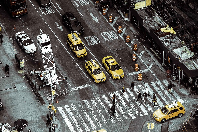 people crossing street on pedestrian with stopping cars photo