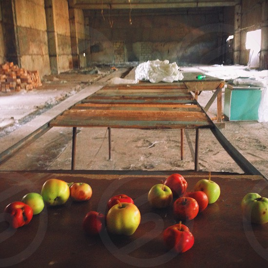 red and yellow apples on brown table photo
