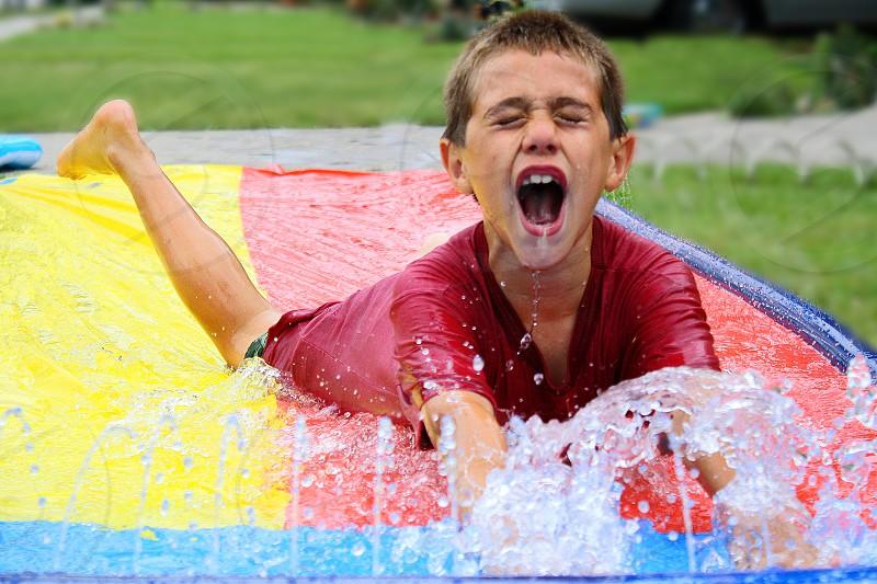 Little boy yells as he gets wet on a slippery wet plastic. photo