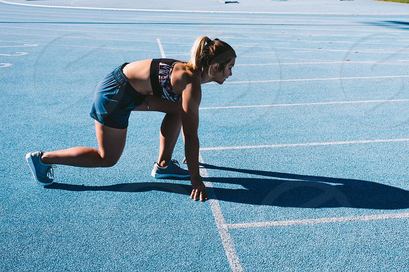 Fit female athlete sprinting on running track photo