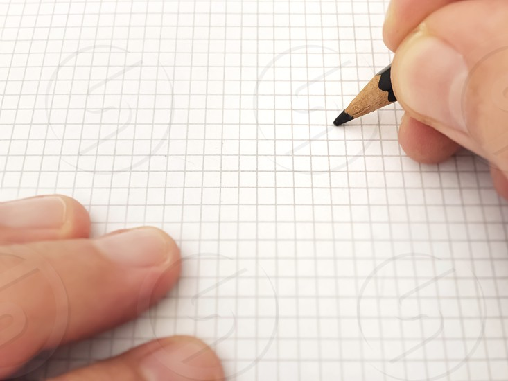 Writing with a pencil on a white sheet of squared paper  photo