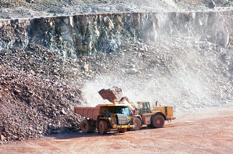 earthmover loading dumper truck with porphyry rock. mining industry. photo