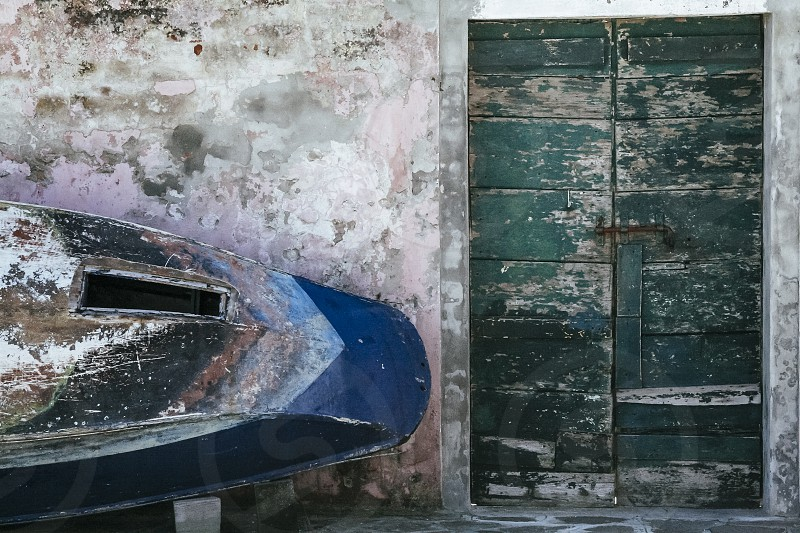 old fishing boat against wall burano venice italy patina painted cropped photo