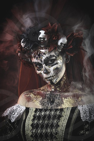 Santa Muerte Young Girl with Artistic Halloween Makeup and with Sculls in her Hair photo