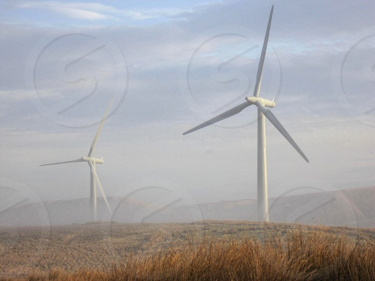 2 wind turbines in a misty rural setting... photo