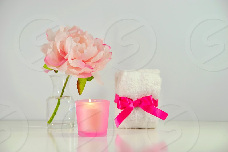Pink peony flower with a candle and small towels wrapped with pink ribbon. photo