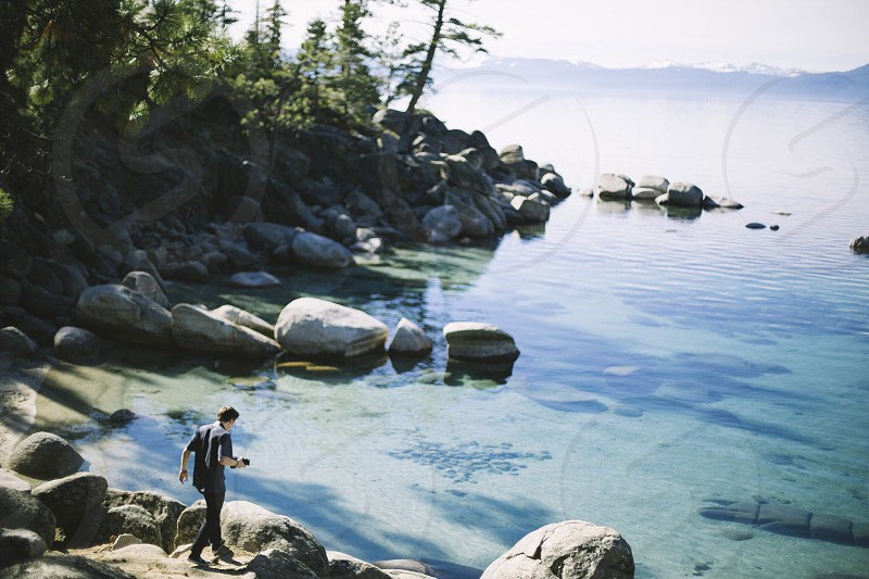 person white and black t shirt and black pants walking on grey rock leading to clear calm shallow boy of water during daytime photo