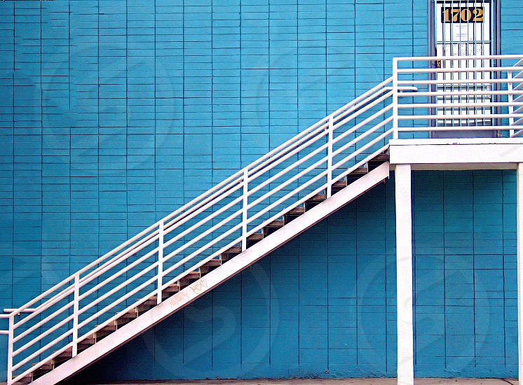 White exterior stairs against a exterior blue brick wall lead to a white door photo