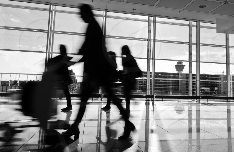 Black and white photo of blurred people rushing in airport photo