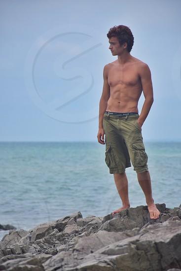 man wearing green cargo shorts standing on gray rock during daytime photo