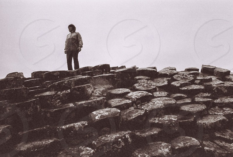 person on grey rocky hill in greyscale photo
