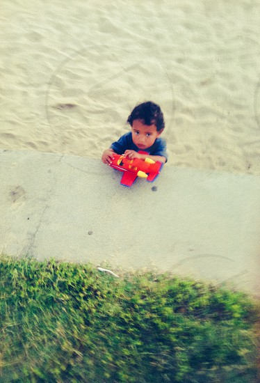 boy in gray t shirt playing a red and yellow plane toy on the seashore photo