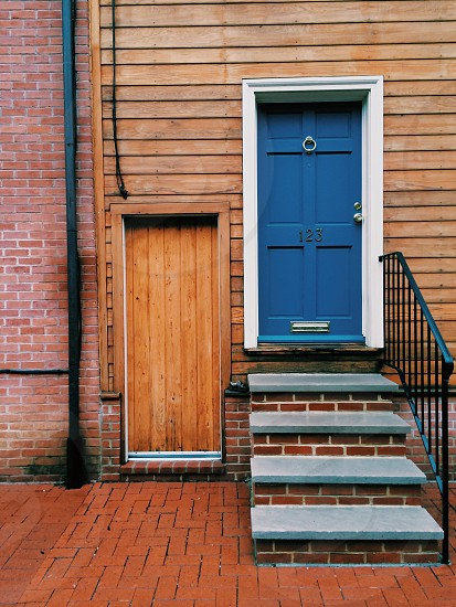 wood siding house with a blue door at the top of brick steps next to a wood door photo