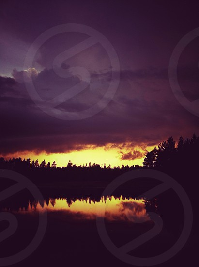 sunset over lake with purple clouds photo