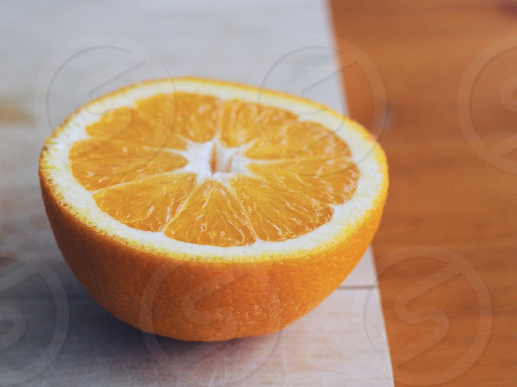 Half orange on a wooden cutting board and table photo
