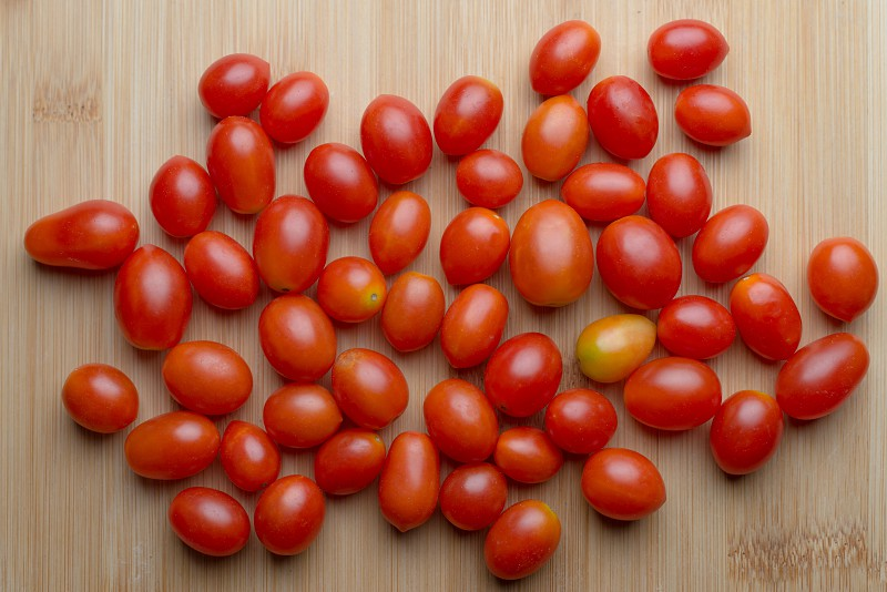 Red ripe tomatoes on wooden table photo