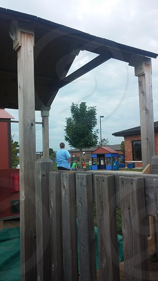 Person watching female standing playground equipment children trees outside  photo