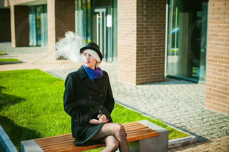 portrait of young beautiful woman with white hair in a black coat a skirt and a black hat smoking an electronic cigarette blowing the smoke vapor photo