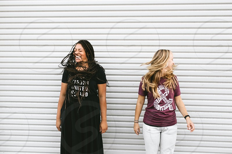 smiling woman in black dress near woman in maroon & t-shirt whipping their hair during daytime photo