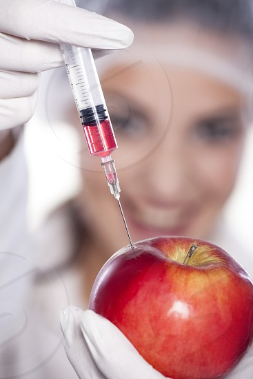 smiling malicious chemist woman injected some liquid in apple photo
