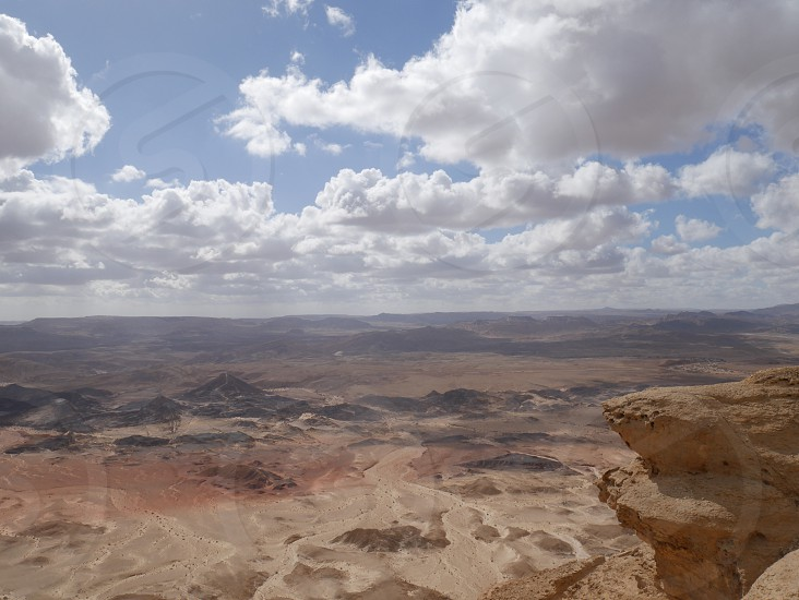 clouds appear over desert scenery looking from crater rim photo